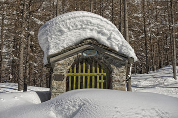 Small mountain chapel in snow background winter time