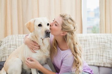 Beautiful blonde relaxing on the couch with pet dog