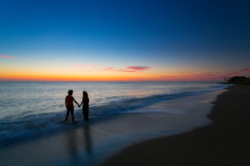 Young couple holding hands on sunrise with water moving