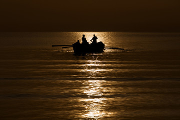 Silhouette of fishermen on the sea at sunrise