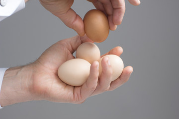 Two hands  with four hens eggs