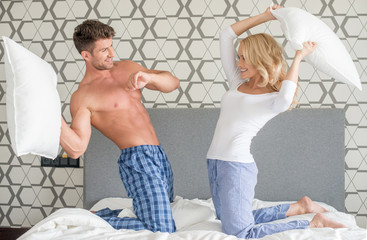 Playful couple having a pillow fight