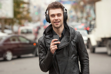 man in headphones on the street. Standing with phone in hand