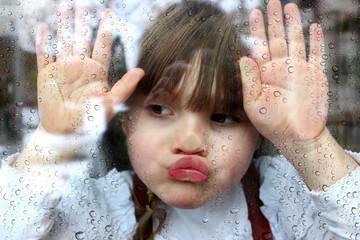 Novembertag: Portrait Mädchen klebt mit Gesicht und Händen an Fensterscheibe mit Regentropfen