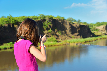 Girl taking river photo by camera, vacation in South Africa