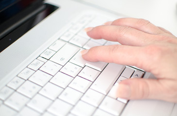 Female hand typing on a white keyboard