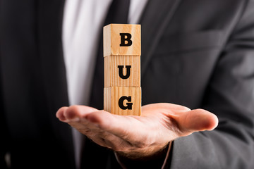 Businessman holding wooden blocks with the word Bug