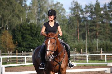 Portrait of woman riding chestnut horse
