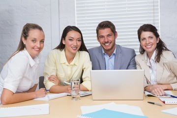Smiling business team having a meeting using laptop