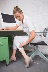 Businesswoman suffering from leg pain at office desk