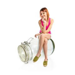 Redhead girl sitting on glass jar over white background