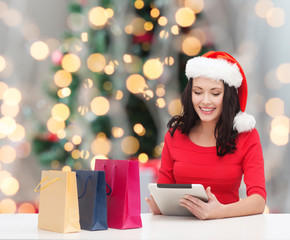 smiling woman in santa hat with bags and tablet pc