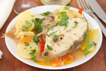 boiled fish with vegetables on white plate