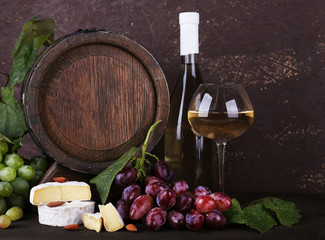 Wine in bottle and in goblet, Camembert and brie cheese, grapes