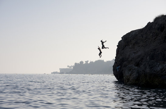 People jumping into the water from cliff