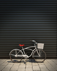 white retro bicycle in front of garage wall