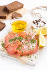 appetizer - salted salmon and bread on a wooden board, vertical