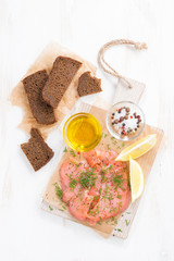 salted salmon, bread and ingredients on a wooden board, top view