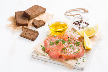 salted salmon, bread and ingredients on a wooden board