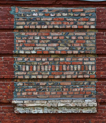 Bricked-up window in the wall of a brick house.