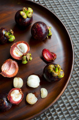 Wooden tray with fresh purple mangosteen