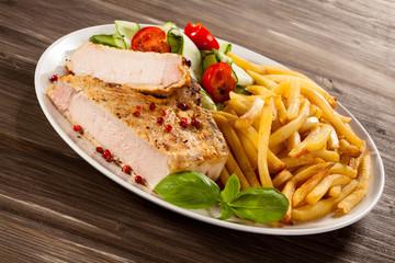 Fried pork chop, chips and vegetable salad