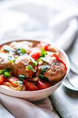 Pasta with meatballs on rustic background