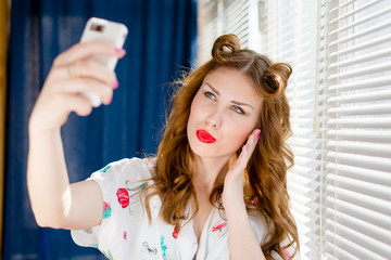 Beautiful young pinup woman taking selfie photo with smart phone