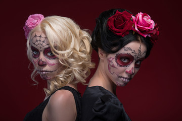 Portrait of two young girls in black dresses with Calaveras make