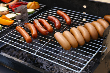 Sausages and vegetables on barbecue grill, close-up