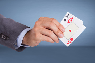 Hand holding aces cards