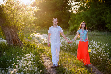 young beautiful couple walking outdoors at sunset