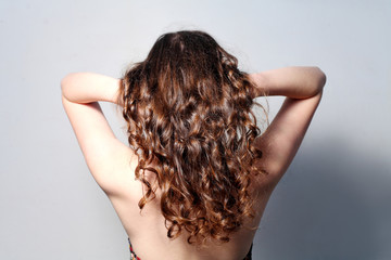 Rear view of curly haired nude women