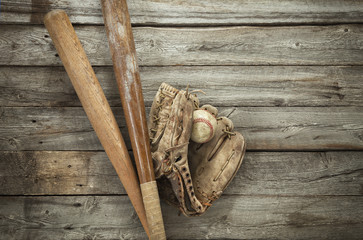 Old baseball with mitt and bats on rough wood