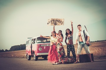 Multi-ethnic hippie hitchhikers with guitar and luggage