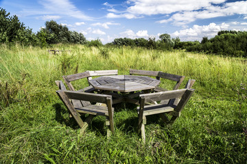 Rustic picnic bench in uncultivated meadow with blue sky