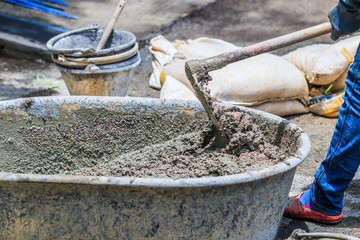 Construction worker is mixing cement
