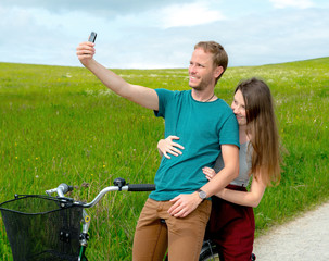 young man and woman on bicycle take a selfie