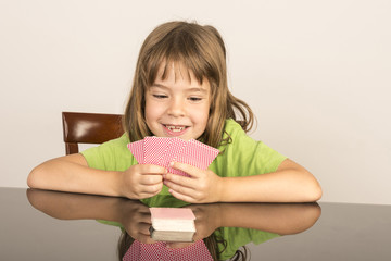 little girl playing cards