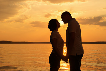 Young romantic couple look to each other during sunset on the be