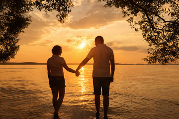 Silhouette of romantic couple walk at sunset