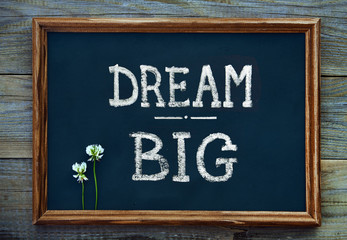 Hand drawn chalkboard sign DREAM BIG over old wooden table backg