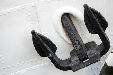 Black bow anchor on old white moored ship