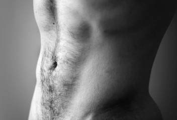 Flat sporty male belly. Closeup black and white photo with shall