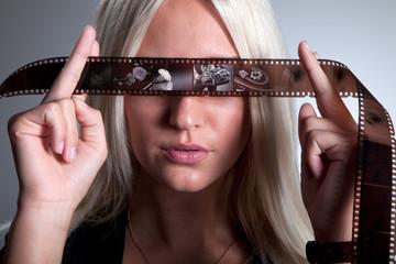 Frau blickt durch Filmstreifen und hat Kopfkino