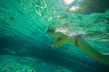 Young woman snorkeling in crystal clear laguna water on tropical