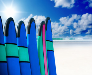 Color surf boards in a stack by ocean