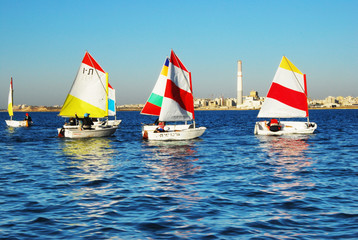 Сhildren learn to sail on Optimist Sailboat