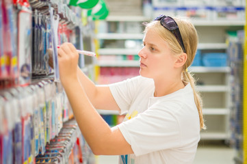 Young woman select writing tools in stationery department in sup
