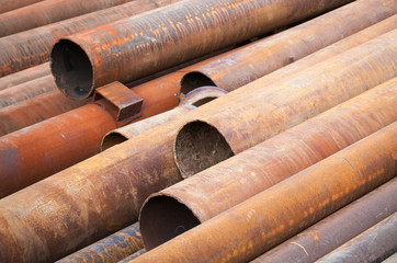 Rusted industrial steel pipes lay on the ground